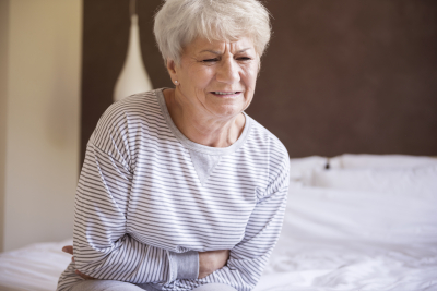 senior woman having a morning pain of the stomach